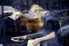 Dos mujeres jovenes de los estudiantes en libros de una lectura de la biblioteca Nea que se sienta Foto de archivo