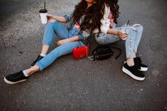 Dos mujeres jovenes de moda se sientan de lado a lado, vestido en un equipo del dril de algodón, las camisetas brillantes, café a Imágenes de archivo libres de regalías