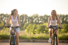 Dos mujeres jovenes de risa que conducen las bicicletas Foto de archivo libre de regalías