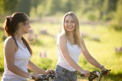 Dos mujeres jovenes del ciclista que se divierten Fotos de archivo libres de regalías