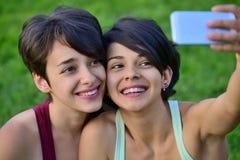 Dos mujeres jovenes del pelo corto que toman las fotos con el teléfono Imagenes de archivo