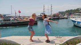 Dos mujeres jovenes despreocupadas felices que saltan en el embarcadero del verano con los yates en el fondo almacen de video