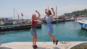 Dos mujeres jovenes despreocupadas felices que saltan en el embarcadero del verano con los yates en el fondo almacen de metraje de vídeo