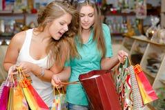 Dos mujeres jovenes emocionadas felices con los bolsos de compras Imagen de archivo libre de regalías