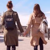 Dos mujeres jovenes en capas y mochilas elegantes que caminan abajo de la calle que lleva a cabo las manos entonado Fotos de archivo libres de regalías