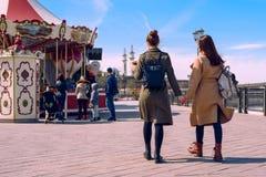 Dos mujeres jovenes en capas y mochilas elegantes que caminan abajo de la calle que lleva a cabo las manos entonado Imagen de archivo