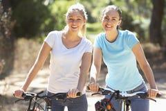 Dos mujeres jovenes en ciclo montan juntas fotos de archivo