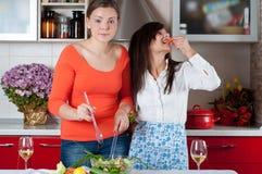 Dos mujeres jovenes en cocina moderna Imagen de archivo libre de regalías