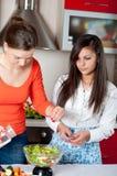 Dos mujeres jovenes en cocina moderna Imágenes de archivo libres de regalías