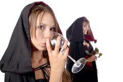 Dos mujeres jovenes en el disfraz Halloween con un vidrio de sangre y Fotos de archivo