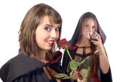 Dos mujeres jovenes en el disfraz Halloween con un vidrio de sangre y Imagen de archivo libre de regalías