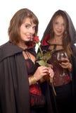 Dos mujeres jovenes en el disfraz Halloween con un vidrio de sangre y Foto de archivo