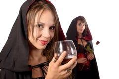 Dos mujeres jovenes en el disfraz Halloween con un vidrio de sangre y Imagen de archivo