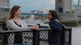 Dos mujeres jovenes en el puente de la torre en Londres - viaje de la ciudad metrajes