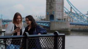 Dos mujeres jovenes en el puente de la torre en Londres - viaje de la ciudad almacen de video