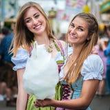Dos mujeres jovenes en el vestido o el tracht del Dirndl, sonriendo con seda del caramelo de algodón en el Oktoberfest Fotografía de archivo
