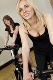 Dos mujeres jovenes en las bicis de ejercicio en la gimnasia Fotografía de archivo libre de regalías