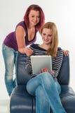 Dos mujeres jovenes en los vaqueros que aplazan una tableta Imagen de archivo