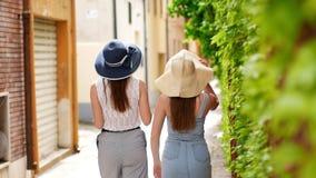 Dos mujeres jovenes en panamas que caminan en la calle de la ciudad a lo largo de la pared verde almacen de video
