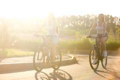 Dos mujeres jovenes en paseo de la bicicleta en luz del sol Imagenes de archivo