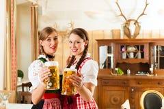 Dos mujeres jovenes en Tracht bávaro tradicional en restaurante o pub Imágenes de archivo libres de regalías