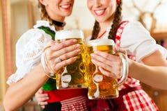 Dos mujeres jovenes en Tracht bávaro tradicional en restaurante o pub Imagen de archivo