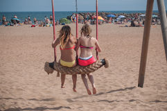 Dos mujeres jovenes en traje de baño en un oscilación en la playa Imágenes de archivo libres de regalías