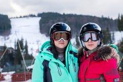 Dos mujeres jovenes en trajes de esquí, con los cascos y las gafas del esquí se colocan Foto de archivo