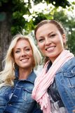 Dos mujeres jovenes en un banco en un parque Foto de archivo