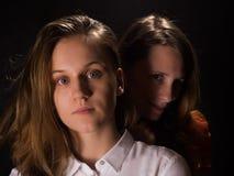 Dos mujeres jovenes en un fondo negro fotos de archivo