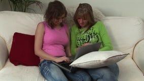 Dos mujeres jovenes en un sofá almacen de video