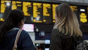 Dos mujeres jovenes en una estación de tren que comprueban horas de salida almacen de metraje de vídeo