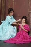 Dos mujeres jovenes en vestidos retros Fotos de archivo libres de regalías