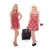 Dos mujeres jovenes en vestidos rojos con la maleta lista para vacation i Fotos de archivo