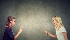 Dos mujeres jovenes enojadas que luchan el griterío en uno a Foto de archivo libre de regalías