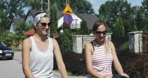 Dos mujeres jovenes están caminando con los cochecitos en la calle metrajes