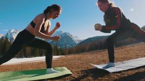 Dos mujeres jovenes están estirando sus piernas contra la perspectiva del bosque y de las montañas almacen de video