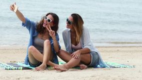 Dos mujeres jovenes están tomando un selfie con un teléfono en la playa en un día soleado metrajes