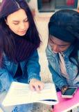 Dos mujeres jovenes estudian en un banco imagen de archivo libre de regalías
