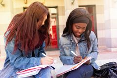 Dos mujeres jovenes estudian en un banco fotografía de archivo