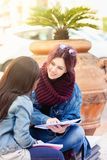 Dos mujeres jovenes estudian en un banco imagen de archivo