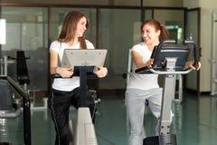 Dos mujeres jovenes felices en biking de la gimnasia Fotografía de archivo libre de regalías