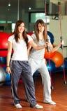Dos mujeres jovenes felices en la gimnasia Imagen de archivo