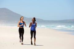 Dos mujeres jovenes felices que activan en la playa Fotografía de archivo