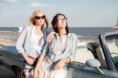 Dos mujeres jovenes felices que se colocan y que esperan cerca del cabriolé Fotos de archivo libres de regalías