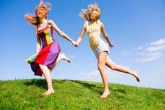 Dos mujeres jovenes felices runing en un campo Imagenes de archivo