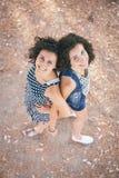Dos mujeres jovenes hermosas abrazadas y que miran para arriba Imagen de archivo libre de regalías