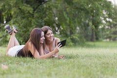 Dos mujeres jovenes hermosas con una tableta en naturaleza Imagen de archivo libre de regalías