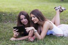 Dos mujeres jovenes hermosas con una tableta en naturaleza Fotos de archivo libres de regalías