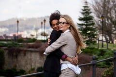 Dos mujeres jovenes hermosas en los trajes que se abrazan Ubicación del parque Imagenes de archivo